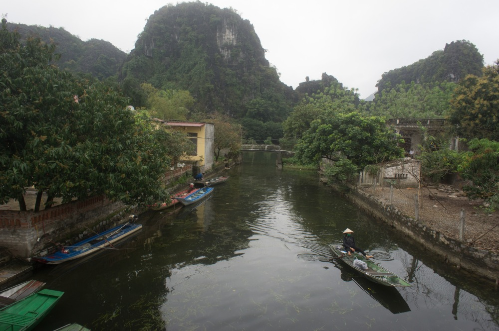 A woman paddling a boat with her feet in Tam Coc.